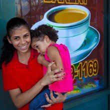 "View ""Young woman holds baby in front of coffee shop"""